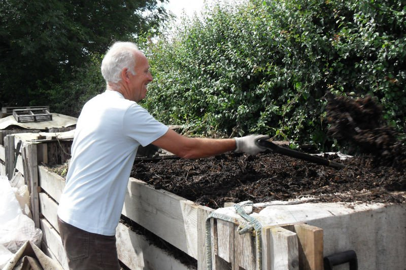 Man shovelling soil in a compost area